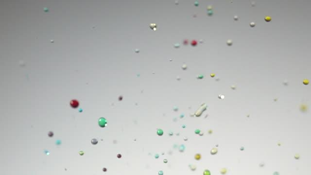 スローモーションで白い背景にカラフルな水染料ダンス - はずむ点の映像素材/bロール