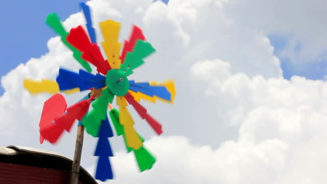 colorful windmill spinning  against blue sky - stick plant part stock videos & royalty-free footage