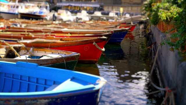Colorful wooden rowboats moored in marina, Naples, Italy