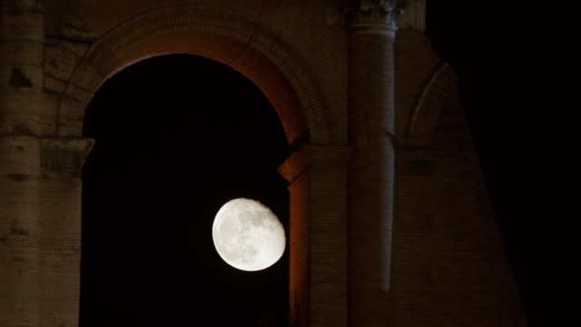 ms colosseum at night, moon in background / rome, italy - colosseo video stock e b–roll