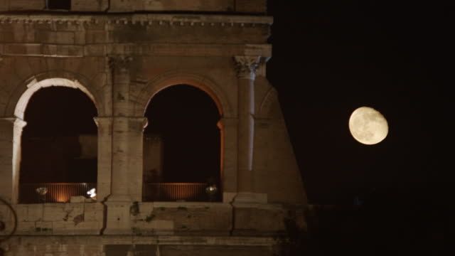 ws colosseum at night, moon in background / rome, italy - das alte rom stock-videos und b-roll-filmmaterial
