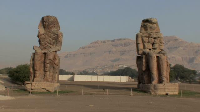 vídeos de stock, filmes e b-roll de ws colossi of mnemnon on west bank of nile, luxor, egypt - figura masculina