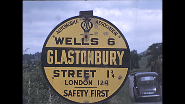 colour archival clip of the aa road sign for glastonbury in somerset home to the world famous music festival / vintage hay truck drives past - road sign stock videos & royalty-free footage