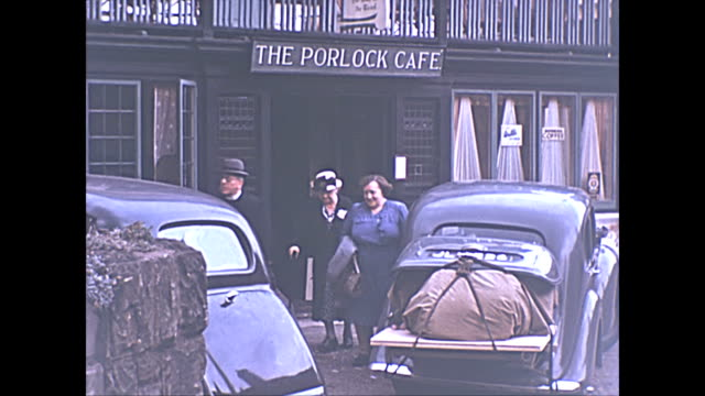 colour archival footage of porlock village in somerset: visitors leave the porlock cafe / views of the village. - ポーロック点の映像素材/bロール