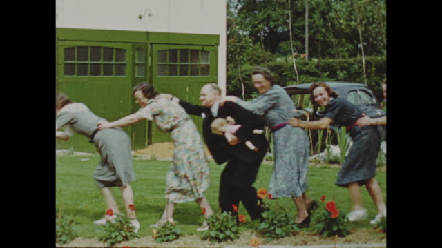 colour archive home movie footage of british home life circa 1940s cu man napping woman riding a horse group of people form a conga line in the... - lawn stock videos & royalty-free footage