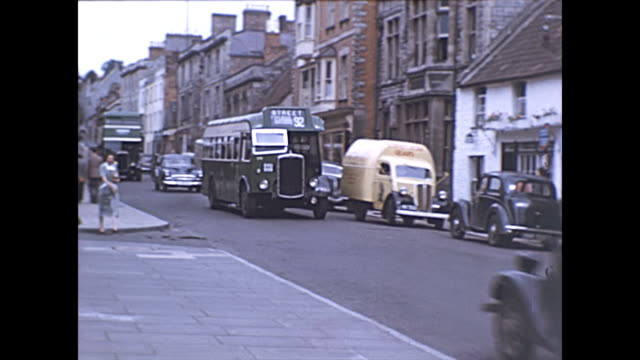 colour footage of glastonbury town. home to the famous music festival. a view up the high street with an unusual van and bus heading towards camera /... - colour image stock videos & royalty-free footage