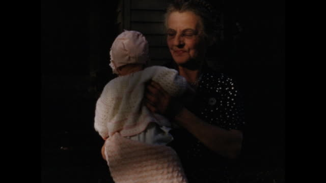 colour home movie footage from 1950s america of a grandmother holding a young baby. - social history stock videos & royalty-free footage