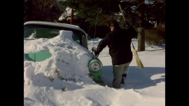colour home movie footage from the 1950s of a street submerged in snow in suburban america a man cleans snow from his car - winter stock videos & royalty-free footage