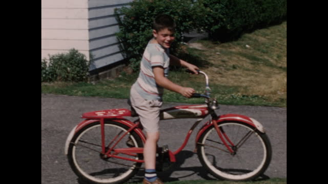 vídeos y material grabado en eventos de stock de colour home movie footage from the 1950s of young children playing outside in suburban america. - bicicleta antigua
