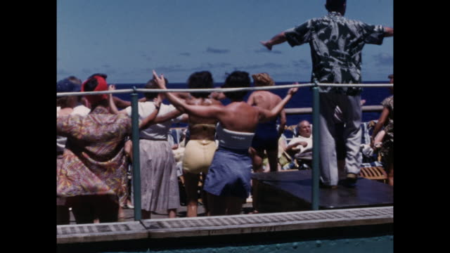 colour home movie footage of scenes of american tourists on a cruise to hawaii including a group dance exercise class, swimming, and posing on the... - stillahavsöarna bildbanksvideor och videomaterial från bakom kulisserna