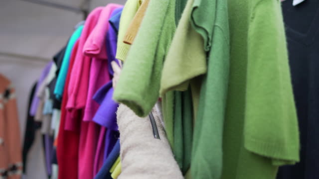 colourful 2nd hand cashmere jumpers for sale on a market stall in portobello road - mercato delle pulci video stock e b–roll