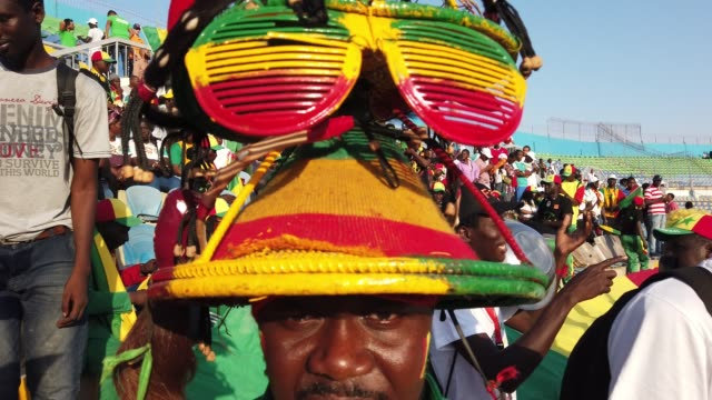 Colourful and vocal Senegal football fan with headgear consisting of a metre high pile of sunglasses and hats during the 2019 African Cup of Nations...