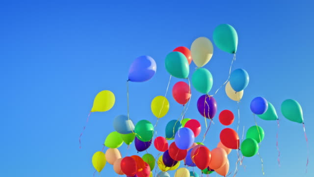 slo mo ld colourful balloons floating across the blue sky - fragility stock videos & royalty-free footage