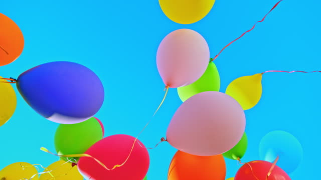 slo mo ld colourful balloons floating into the blue sky - content stock videos & royalty-free footage