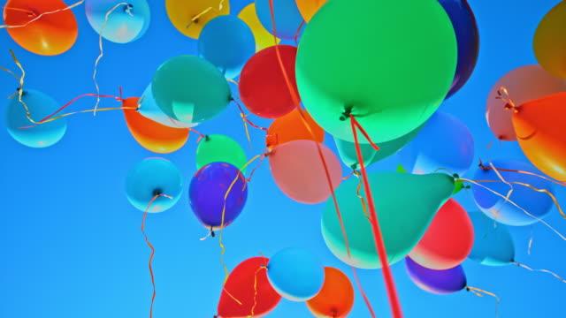 vídeos y material grabado en eventos de stock de slo mo ld globos de colores flotando en el cielo soleado azul - globo de helio