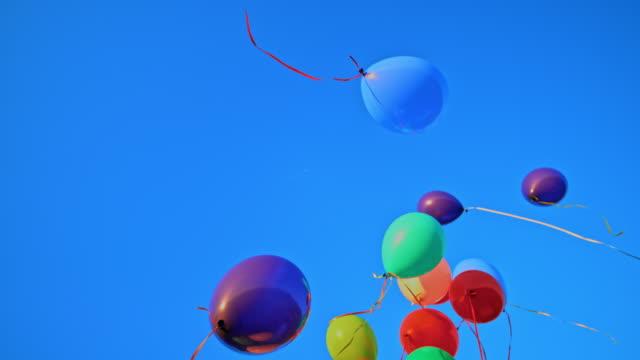 vídeos y material grabado en eventos de stock de slo mo ld globos de colores flotando en el cielo azul - globo de helio