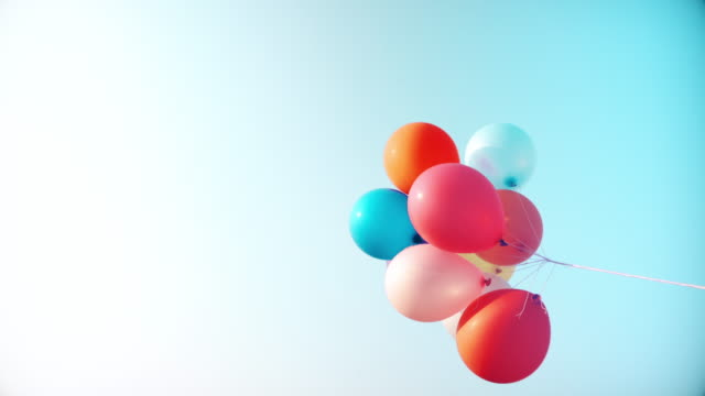 bunte ballons fliegen in der luft mit blauem himmel - multi coloured stock-videos und b-roll-filmmaterial