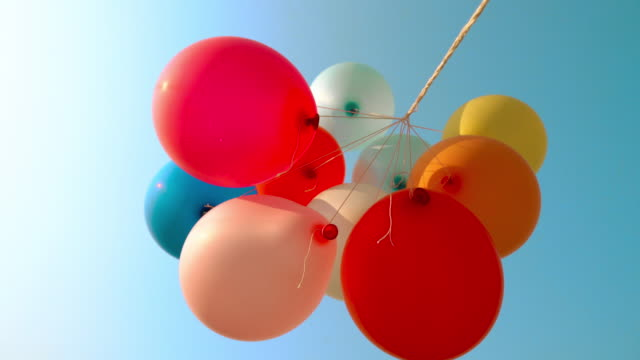 colourful balloons flying in the air with blue sky - single object stock videos & royalty-free footage