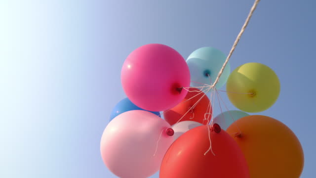 colourful balloons flying in the air with blue sky - anniversary stock videos & royalty-free footage