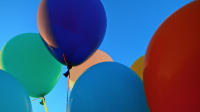 slo mo ld colourful balloons tied together floating into the blue sky - releasing stock videos & royalty-free footage