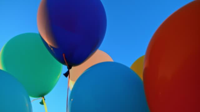 vidéos et rushes de slo mo ld ballons colorés attachés ensemble flottant dans le ciel bleu - laisser partir