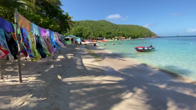 vidéos et rushes de colourful beach stall, shadow of palm trees, white sand, small boats, saltwhistle bay beach, mayreau, grenadines, west indies, caribbean, central america - multicolore