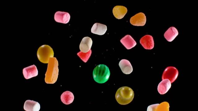 黒い背景に落ちるslo mo ldカラフルなキャンディー - 菓子類点の映像素材/bロール