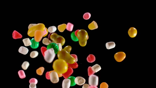 slo mo ld colourful candy flying into the air - confectionery stock videos & royalty-free footage