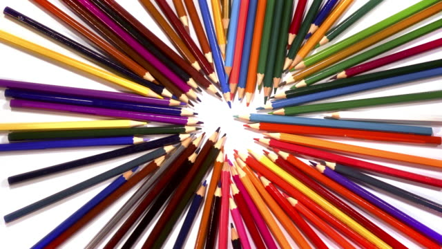 A colourful collection of pencils spin to reveal a white background.