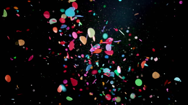 slo mo ld colourful confetti and glitter flying in the air against black background - slow motion stock videos & royalty-free footage