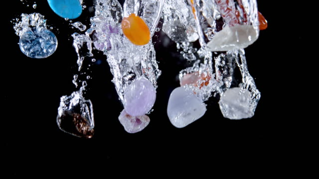 slo mo ld colourful crystals falling into the water on black background - medium group of objects stock videos & royalty-free footage