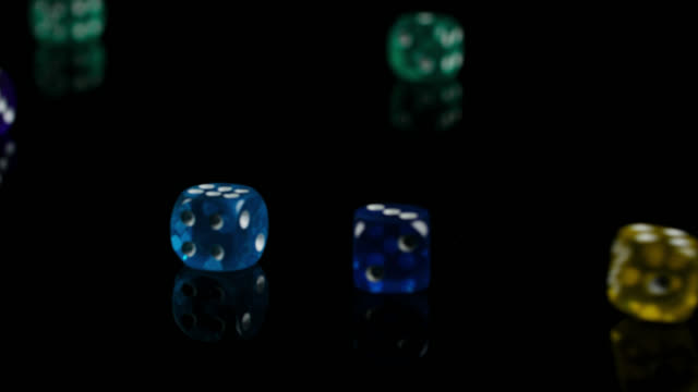 colourful dice fall on black reflective surface - dice stock videos & royalty-free footage