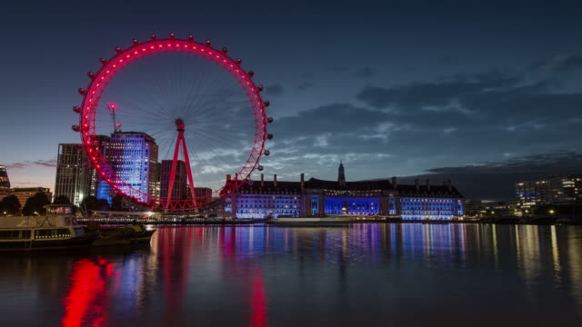 colourful lights reflect off the water as clouds build overhead during a night to day timelapse transition looking across the river thames towards the london eye and county hall - riverbank stock videos & royalty-free footage