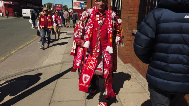a colourful liverpool supporter walks towards the camera outside anfield dressed head to toe in liverpool football club flags scarves badges prior to... - flag stock videos & royalty-free footage