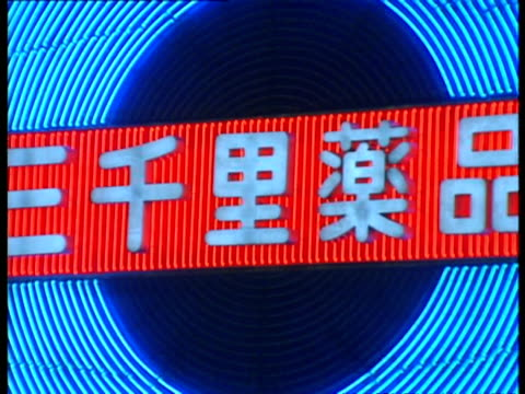 cu colourful neon sign pulsing, blue concentric circles crossed by japanese lettering, tokyo - moving image stock videos & royalty-free footage