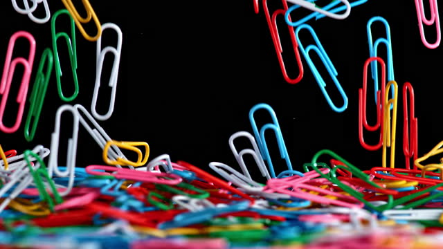 slo mo ld colourful paper clips falling onto a surface and piling up - group of objects stock videos & royalty-free footage