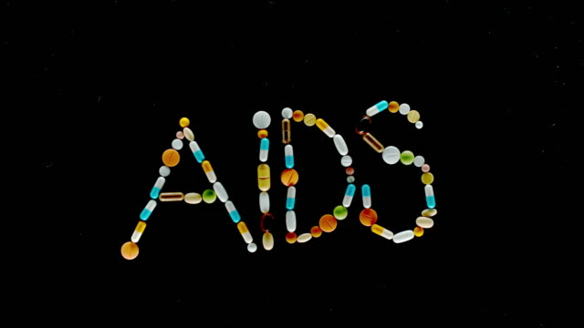 """slo mo ld colourful pills, tablets and capsules falling onto a black surface and making an inscription """"aids"""" - capital letter stock videos & royalty-free footage"""