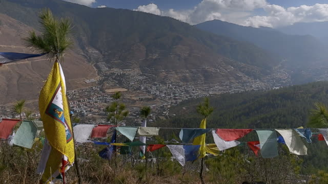 colourful prayer flags are tied on lines in front of the city of thimphu - thimphu stock videos & royalty-free footage