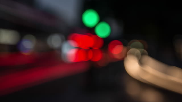 colourful soft focused abstracted streetlights and blurred flowing traffic move through the frame at dusk - beliebiger ort stock-videos und b-roll-filmmaterial