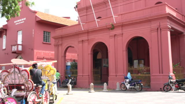 vidéos et rushes de colourful tourist rickshaws in front of the red christ church in the historical centre of the city of malacca, malaysia - pousse pousse