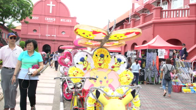 colourful tourist rickshaws waiting for tourists in front of the red christ church in the historical centre of the city of malacca, malaysia - malacca stock videos and b-roll footage