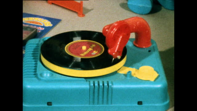 colourful toy record player plays small record; 1976 - part of a series stock videos & royalty-free footage