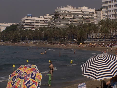 Colourful umbrellas shade a beach flanked by hotels in Costa Del Sol Spain.