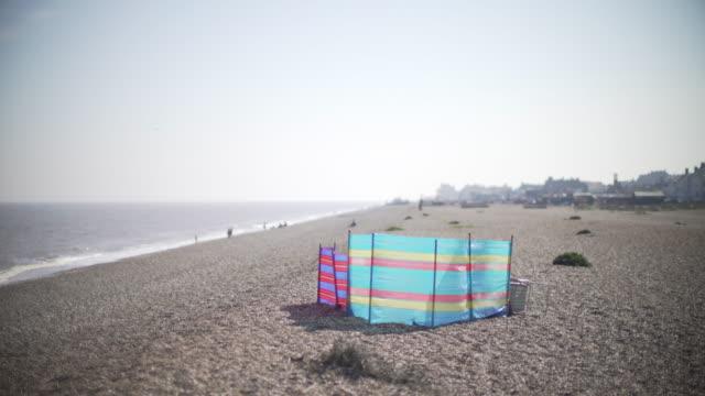A colourful windbreak on the beach at Aldeburgh in Suffolk, UK