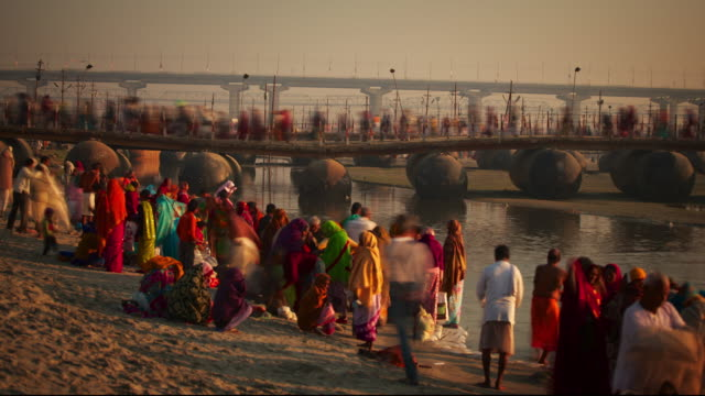 a colourfully dressed crowd stand beside the river ganges - pellegrino video stock e b–roll