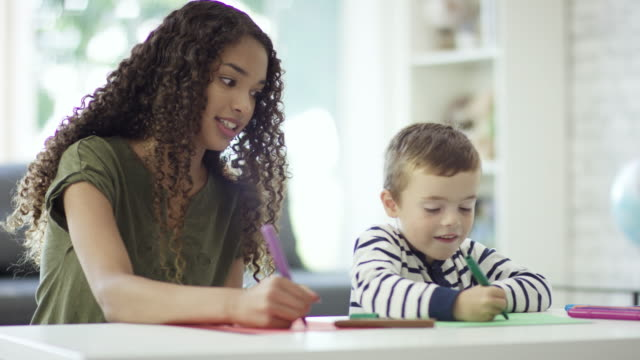 colouring with the babysitter - nanny stock videos & royalty-free footage