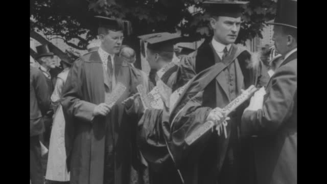 columbia faculty wearing caps and gowns in procession outside / guglielmo marconi with maybe a faculty member wearing glasses; they hold papers,... - east asian ethnicity stock videos & royalty-free footage