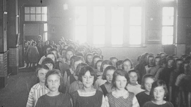 1925 montage column of elementary schoolgirls file in to assembly hall and with hands clasped in prayer the head master leads them in morning devotion / newcastle upon tyne, england, united kingdom - praying stock videos & royalty-free footage