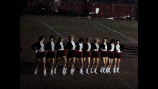 column of females dancing in the can can dance formation on a football field. - cheerleader stock videos & royalty-free footage