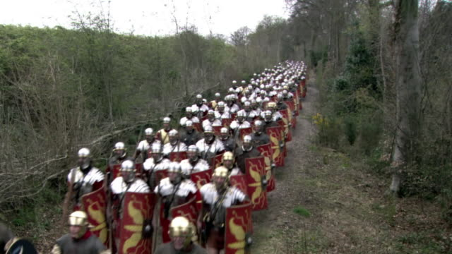 a column of roman soldiers marches through the countryside. - marciare video stock e b–roll